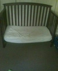 Brown wooden crib frame with matters 231 mi