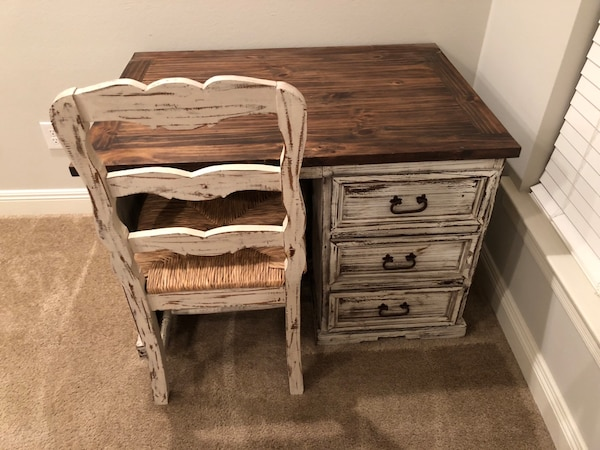 Rustic solid wood desk with wicker wood chair.