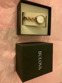 Round silver analog watch with silver link bracelet in box