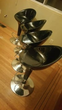 four black-and-silver bar stools