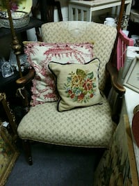 brown wooden framed white and brown floral padded armchair