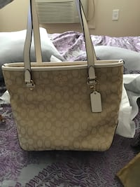 brown and white Coach shoulder bag