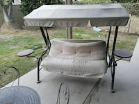 black and beige canopy swing bench
