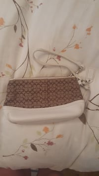 gray and white monogrammed Coach wristlet