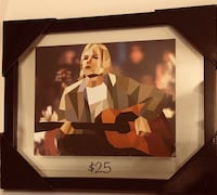 man playing guitar painting with black frame