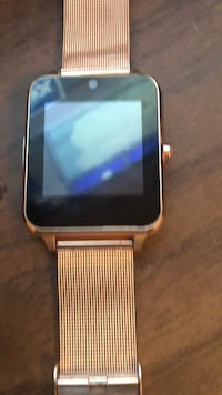 black smartwatch with gold-colored link strap Omaha, 68104