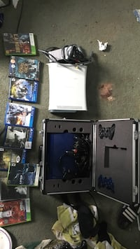 Blue console ps3 and white xbox 360 with controllers and gamees
