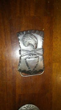 silver-colored eagle and arrowhead belt buckle