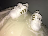 pair of toddler's white-and-gold Adidas velcro strap shoes