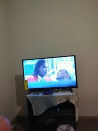 flat screen television with black wooden TV stand Conroe, 77304
