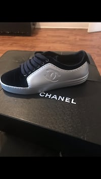unpaired white and black Chanel low-top sneaker with box