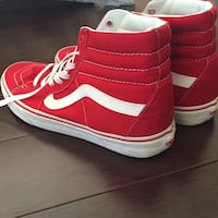 pair of red-and-white Vans high-top sneakers