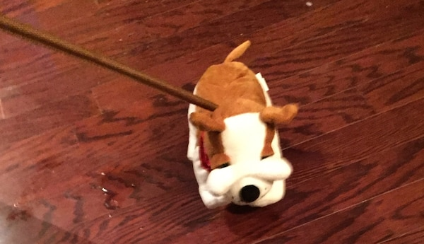 Brown and white walking dog plush toy on stick.