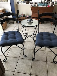 Two black metal framed blue padded chairs and matching glass table.