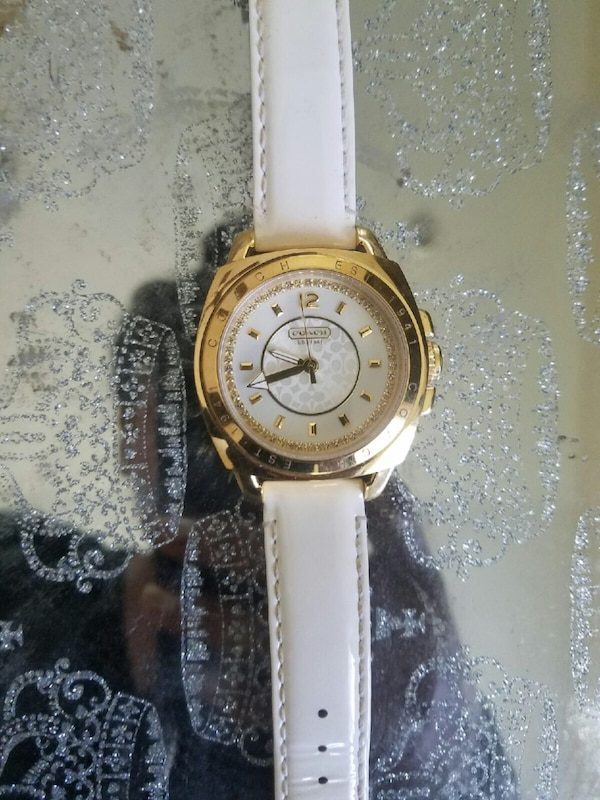 Round gold analog watch with white leather strap coach