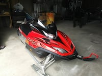 red and black snowmobile with a 2k snow suite and