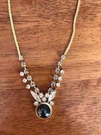 gold-colored necklace with black pendant