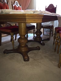 brown wooden pedestal table with two chairs