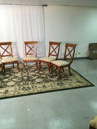 Six brown wooden framed white padded dining chairs