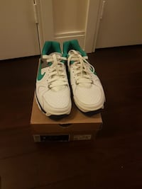 pair of white-and-green Nike low-top sneakers with box