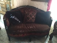Brown wooden framed maroon and brown padded loveseat with throw pillows