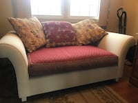 Cream love seat with red cushion