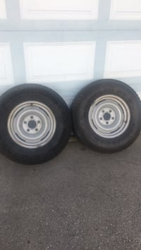 two gray 5-lug vehicle wheels with tires