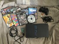 black Sony PS2 console with controllers and game cases