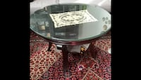 Round brown wooden base with glass-top table