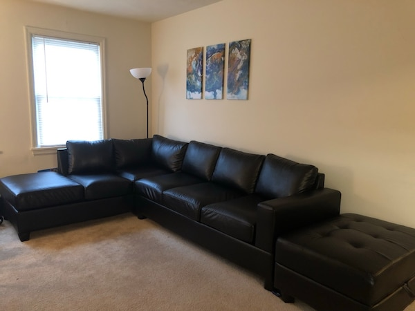 Black leather sectional sofa with ottoman (practically new- no damage)