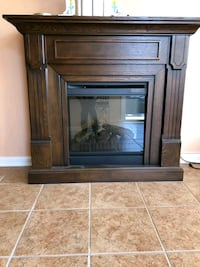 brown wooden framed glass cabinet with portable electric fireplace Pikesville, 21208