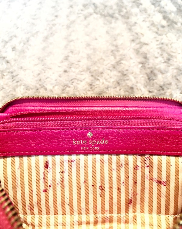 """Kate Spade wallet paid $178 good condition. The wraparound zip opens to a lined interior with a dividing zip pocket, checkbook compartment, 2 bill slots, and 12 card slots. Exterior back pocket. Measurements 7 ¾""""W x 4""""H x 1""""D. Has minor imperfections in o 79391153-4553-4d5c-b468-c2cdc7948d50"""