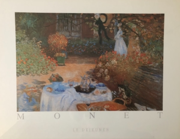 "Large print of Claude Monet's ""Le Dejeuner"" (""The Lunch,"" 1873) in gold frame with glass."