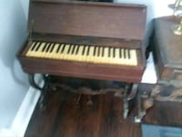 brown wooden upright piano with chair