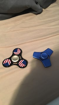 two black and blue fidget spinners that are metal