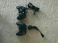 two black Xbox corded controllers
