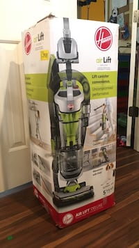 black and green Bissell upright vacuum cleaner with box