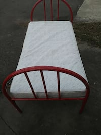 white and gray mattress and red metal bed frame