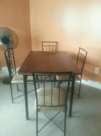 rectangular brown wooden table with four chairs