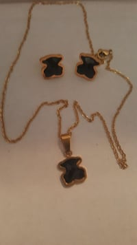 gold-colored necklace with black pendant and pair of gold-colored earrings
