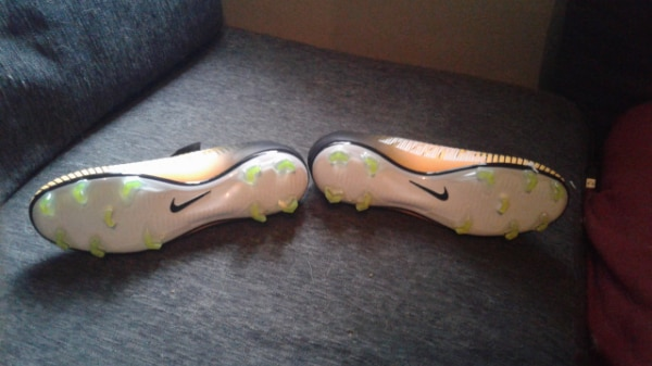pair of white-and-orange Nike cleats 82331731-a553-422d-9f6c-c9b29b4a6bd3