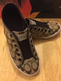 pair of brown monogrammed Coach slip-on shoes