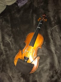 Brown and black violin with bow and black case it's small