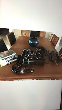 Black xbox 360 game console with controllers, 6 games and headphones and a wireless network adapter