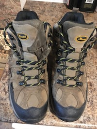Pair of brown-and-black hiking boots. They are 100% water proof and very firm. Vancouver, V6G 1T1