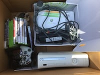 white Xbox 360 console with controller and game cases