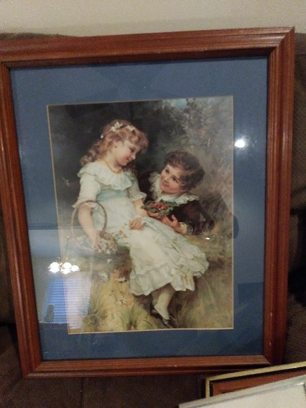 girl in white dress and boy in brown tops on grass field painting with brown wooden frame