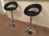 Two black leather padded with stainless steel bases bar stoop chairs
