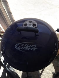 Weber charcoal grill with bud light beer logo.