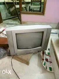 gray CRT TV with brown wooden TV hutch